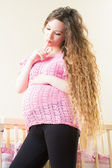 Pregnant woman with long hair near crib — Stock Photo