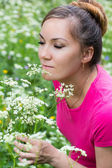 Portrait of beautiful young woman with flowers on nature in summer — Stock Photo