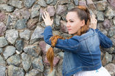Close up of portrait sexy beautiful woman in jeans jacket on stones — Stock Photo