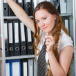 Business theme:  portrait of happy woman in office, standing with folder, s — Stock Photo