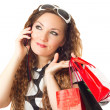 Portrait of young woman with shopping bags and long hair on white backgroun — Stock Photo