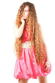 Beautiful woman with long curly hair in pink dresson white background More — Stock Photo