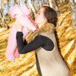 Happy young mother playing with little daughter in autumn park — ストック写真