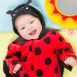 Royalty-Free Stock Photo: Pretty baby girl, dressed in ladybug costume on green background. The concept of childhood and holiday