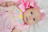 A cute little newborn baby girl in pink bow and dress on a bed — Stock Photo