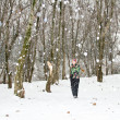 Woman in ski suit on tree in snowy winter outdoors in Kazakhstan - Stock Photo