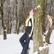 Woman in ski suit on tree in snowy winter outdoors in Kazakhstan - Stockfoto