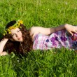 Young beautiful girl laying on the  flowers dandelions, outdoor portrait, summer fun concept — Lizenzfreies Foto