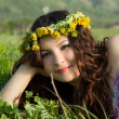 Beautiful womanl at the wreath lies on the grass, summer fun concept - Zdjcie stockowe