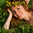 Beautiful womanl at the wreath lies on the grass, summer fun concept — Stock Photo #14922755