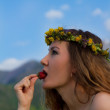 Beautiful woman eating strawberries on blue sky background — Stock Photo #14922799