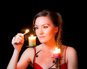 Woman wonders with a candle on Christmas night — Stock Photo