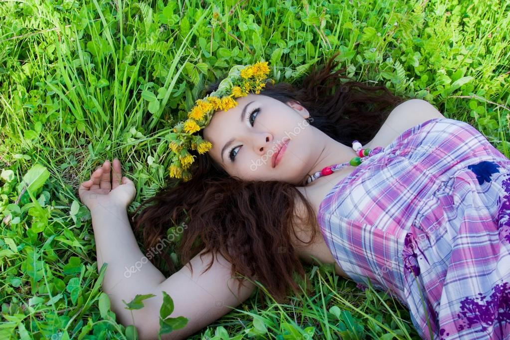 Young beautiful girl laying on the  flowers dandelions, outdoor portrait, summer fun concept — Stock Photo #14922623