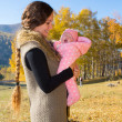 Mother and daughter spending time outdoor in the autumn park — Stock Photo #15686041
