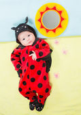 Pretty baby girl, dressed in ladybug costume on green background The concept of childhood and holiday — Stock Photo