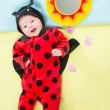 Pretty child girl, dressed in ladybug costume on green background  The concept of childhood and holiday - Stock Photo