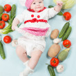 Portrait of smiling baby wearing a chef hat  surrounded by vegetables. Use it for a child, healthy food concept — Stock Photo