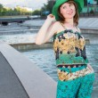 Attractive young woman in green hat on embankment in summer in city - Photo