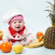 Portrait of smiling baby wearing a chef hat surrounded by fruits. Use it for a child, healthy food concept — Stock Photo