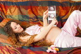 Pregnant woman and belly with the ultrasound images in hands at home. The concept of health and medicine — Fotografia Stock