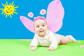 Pretty child girl, dressed in butterfly costume on green background and sun — Stock Photo