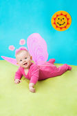 Pretty child girl, dressed in butterfly costume on green background and sun. The concept of childhood and holiday — Stock Photo