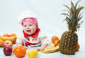 Portrait of smiling baby wearing a chef hat surrounded by fruits. Use it for a child, healthy food concept — Foto Stock