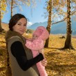 Mother and daughter spending time outdoor in the autumn park — Stock Photo