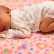Stock Photo: Newborn baby sleeps on bed. Use it for child, parenting or love concept