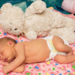 Stock Photo: Newborn baby girl sleeps with toy on bed. Use it for child, parenting or love concept