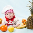 Portrait of smiling baby wearing a chef hat  surrounded by fruits  Use it for a child, healthy food concept — Stock Photo