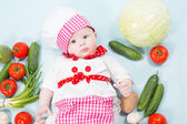 Baby girl wearing a chef hat with vegetables. Use it for a child, healthy food concept — Stock Photo