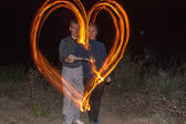 Happy couple painting the heart flames of fire as a symbol of love and family night — Stock Photo