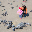 Child girl and mum playing with doves in the city street — Stock Photo