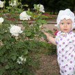 Smiling pretty little child girl with flower rose in park — Stock Photo #26419295