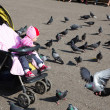 Child girl playing with doves in the city street — Stock Photo