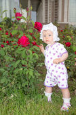 Smiling pretty little child girl with flower rose in park — Stock Photo