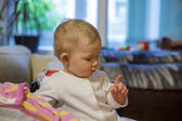 Pretty little child girl looks at his drooling at home — Stock Photo