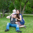 Happy family: mother, father and daughter baby playing in the park — Foto de Stock