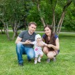 Stock Photo: Happy family: mother, father and daughter baby playing in the park