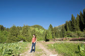 Woman with long hair on nature of green trees and blue sky, near Medeo in Almaty, Kazakhstan,Asia — Stock Photo