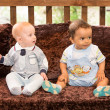 Small two children: black american and caucasian boys siting up on sofa — Stock Photo