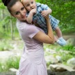 Happy mom and baby boy hugging and laughing. The concept of childhood and family. Beautiful Mother and her Child outdoors — Stock Photo