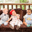 Small three children: black american, caucasian boys and russian baby girl siting up on sofa — Stock fotografie