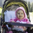 Smiling pretty little child girl in buggy on nature — Stock Photo