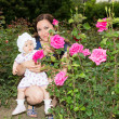 Stock Photo: Happy mom and child girl hugging in flowers. The concept of childhood and family. Beautiful Mother and her baby outdoors