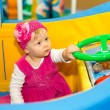 Happy baby girl  keep on board ship on playground — Stock Photo