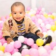 Black boy in colored balls — Stock Photo