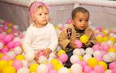 Happy children in colored balls — Stock Photo