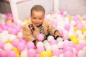 Black boy in colored balls — Zdjęcie stockowe